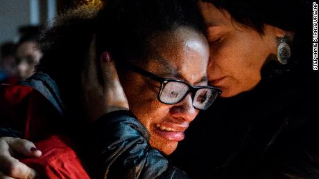 Isabel Kinnane Smith of Taylor Allderdice High School is comforted by Lesley Britton, a math teacher at the school, during a vigil Saturday in Pittsburgh.