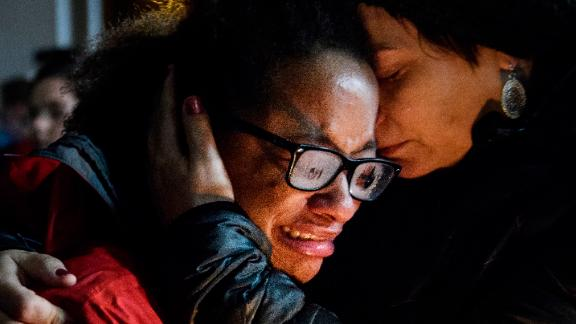 Isabel Kinnane Smith of Allderdice is comforted by Lesley Britton, a math teacher at the school, at a vigil blocks from where an active shooter shot multiple people at Tree of Life Congregation synagogue on Saturday, Oct. 27, 2018, in the Squirrel Hill section of Pittsburgh. (Stephanie Strasburg/Pittsburgh Post-Gazette via AP)