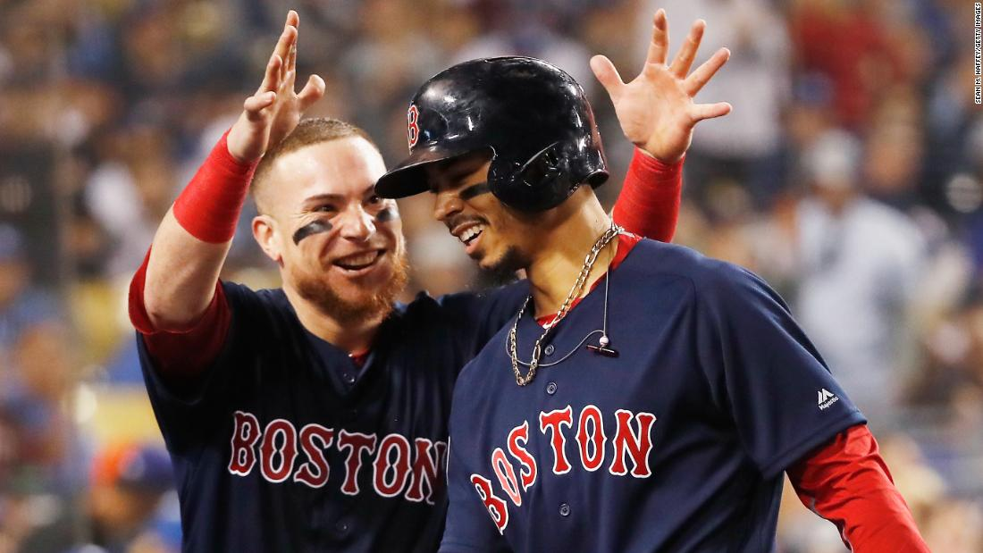 Mookie Betts of the Boston Red Sox is congratulated by his teammate Christian Vazquez after his sixth-inning home run against the Los Angeles Dodgers in Game 5.