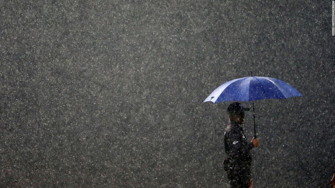 A match official is seen in the rain during a cricket match between Sri Lanka and England on Tuesday, October 23. The match was being played in Colombo, Sri Lanka.