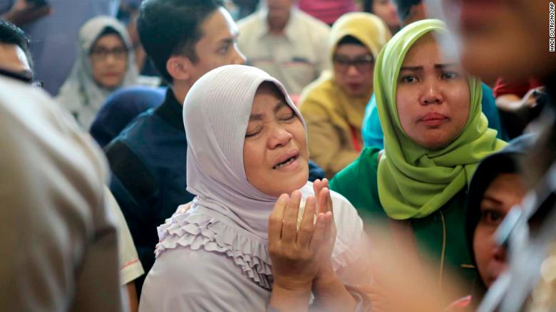A relative of passengers prays as she and others wait for news on the Lion Air plane.