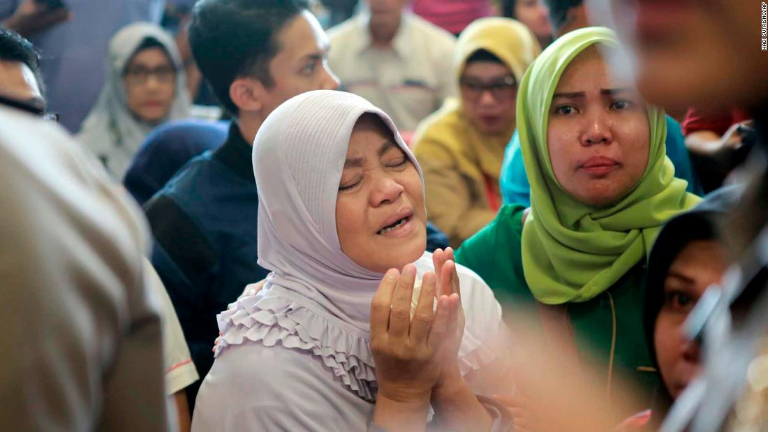 A woman in Pangkal Pinang prays as she and others wait for news on October 29.