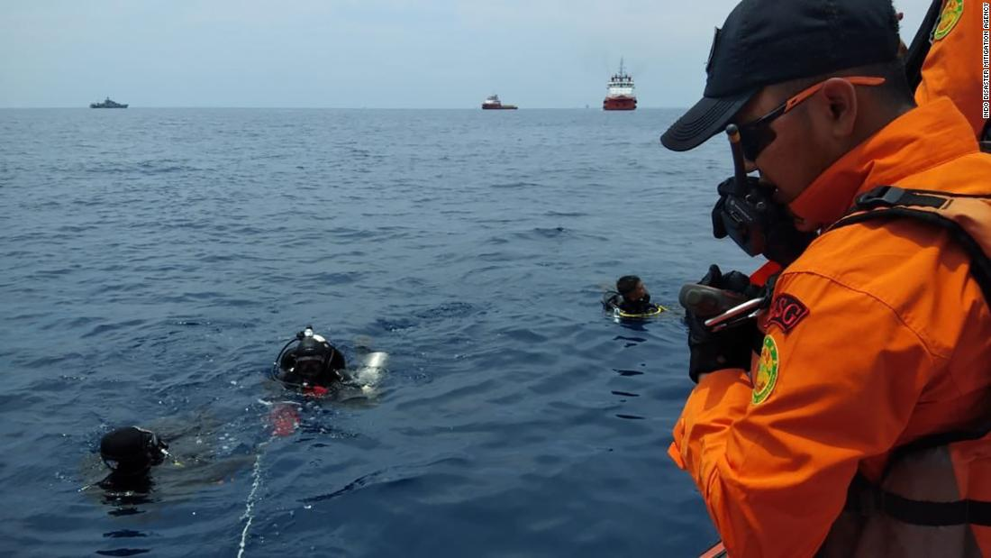 Divers work near the site where an Indonesian passenger plane crashed on Monday, October 29.