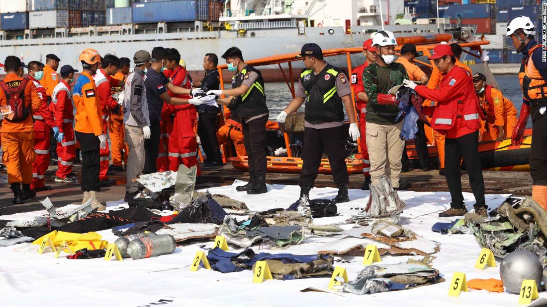 Members of a rescue team bring personal items and wreckage ashore in Jakarta on October 29.