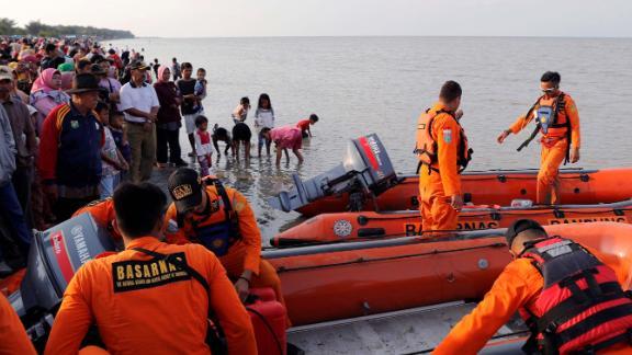 People gather on the beach as a rescue team prepares to leave the coast of Karawang.
