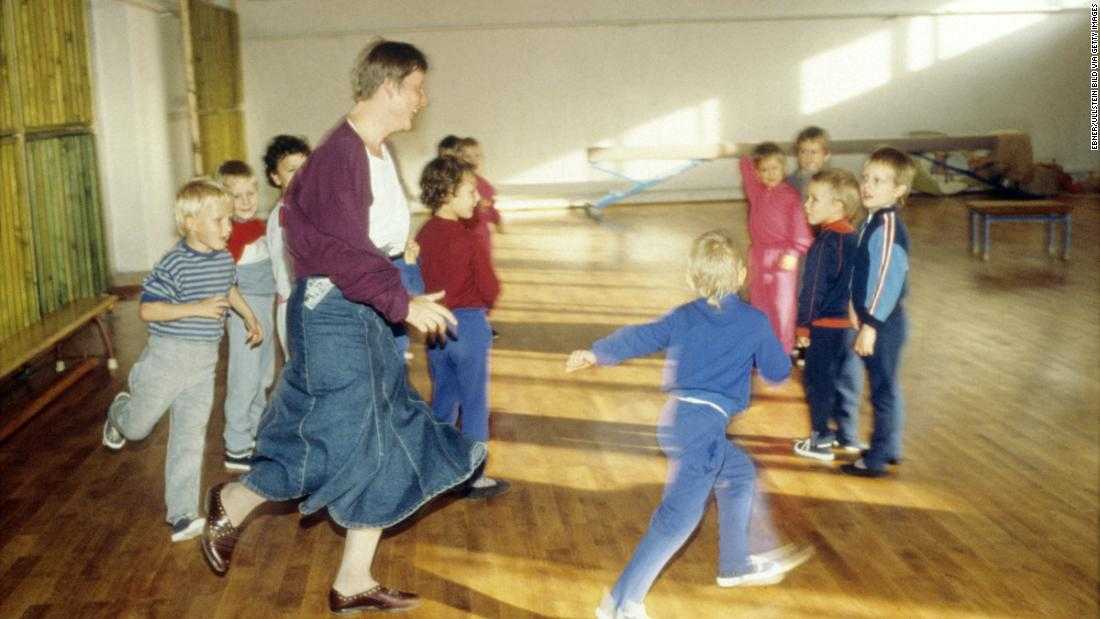 "Merkel visits a children's home during her campaign to become a member of the Bundestag, Germany's parliament, in 1990. Before turning to politics, Merkel had trained as a physician. She was also a spokeswoman for the ""Democratic Awakening,"" East Germany's opposition movement before reunification."
