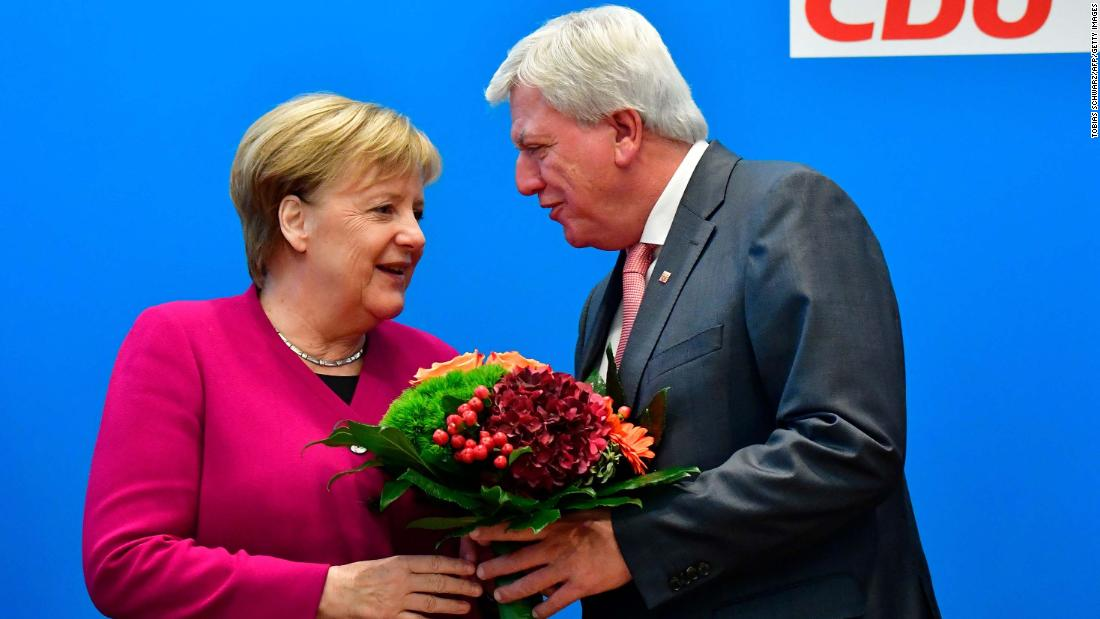 "Merkel offers flowers to Volker Bouffier, the state premier of Hesse and the deputy chairman of the Christian Democratic Union (CDU), ahead of a party leadership meeting at the CDU headquarters in Berlin on October 29. The day before, her coalition government suffered heavy losses in a key regional election in Hesse. Merkel later announced she would <a href=""https://edition.cnn.com/2018/10/29/europe/angela-merkel-germany-election-intl/index.html"" target=""_blank"">not seek re-election</a> when her term expires in 2021."