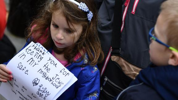 "A girl holds thank-you notes on October 28, 2018 outside of the Tree of Life Synagogue after a shooting there left 11 people dead in the Squirrel Hill neighborhood of Pittsburgh on October 27, 2018. - A man suspected of bursting into a Pittsburgh synagogue during a baby-naming ceremony and gunning down 11 people has been charged with murder, in the deadliest anti-Semitic attack in recent US history. The suspect -- identified as a 46-year-old Robert Bowers -- reportedly yelled ""All Jews must die"" as he sprayed bullets into the Tree of Life synagogue during Sabbath services on Saturday before exchanging fire with police, in an attack that also wounded six people. (Photo by Brendan Smialowski / AFP)        (Photo credit should read BRENDAN SMIALOWSKI/AFP/Getty Images)"