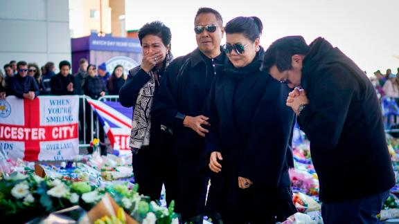 The son and wife ofVichai Srivaddhanaprabha  pray after laying wreathes outside the stadium
