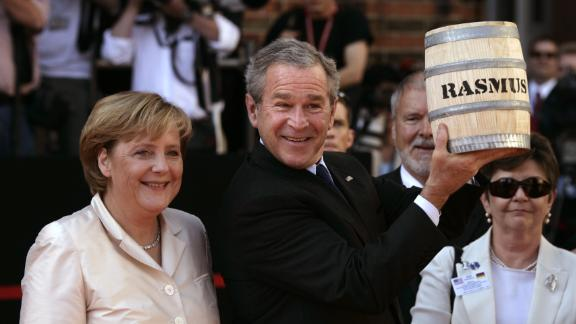 US President George W. Bush shows off a barrel of pickled herrings he was presented after arriving in Stralsund, Germany, in July 2006.