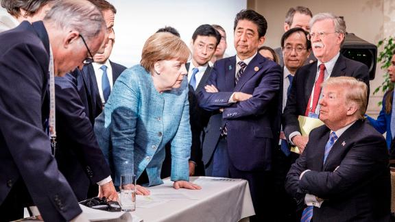 CHARLEVOIX, CANADA - JUNE 9:   In this photo provided by the German Government Press Office (BPA), German Chancellor Angela Merkel deliberates with US president Donald Trump on the sidelines of the official agenda on the second day of the G7 summit on June 9, 2018 in Charlevoix, Canada. Also pictured are (L-R) Larry Kudlow, director of the US National Economic Council, Theresa May, UK prime minister, Emmanuel Macron, French president, Angela Merkel, Yasutoshi Nishimura, Japanese deputy chief cabinet secretary, Shinzo Abe, Japan prime minister, Kazuyuki Yamazaki, Japanese senior deputy minister for foreign affairs, John Bolton, US national security adviser, and Donald Trump. Canada are hosting the leaders of the UK, Italy, the US, France, Germany and Japan for the two day summit.