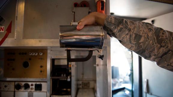An airman holds a hot cup inside a KC-10 Extender at Travis Air Force Base, California, June 21, 2018.