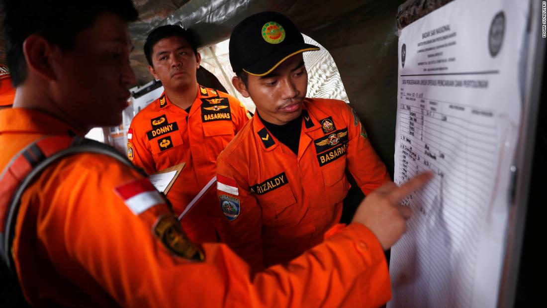 Indonesian rescue team members update a manifest chart on Tuesday, October 30, as they work to retrieve the bodies of those who died in the Lion Air flight JT610 crash.