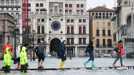 People cross the flooded St. Mark's Square on a raised walkway Monday.