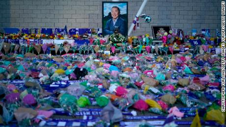 A portrait of Vichai Srivaddhanaprabha surrounded by a sea of tributes