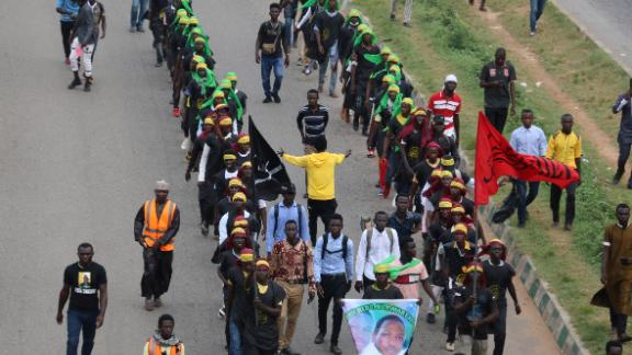 Members of Islamic Movement of Nigeria (IMN) wave flags and chant slogans as they take part in a demonstration to protest against an imprisoned Shiite cleric, in Abuja, on October 29, 2018.