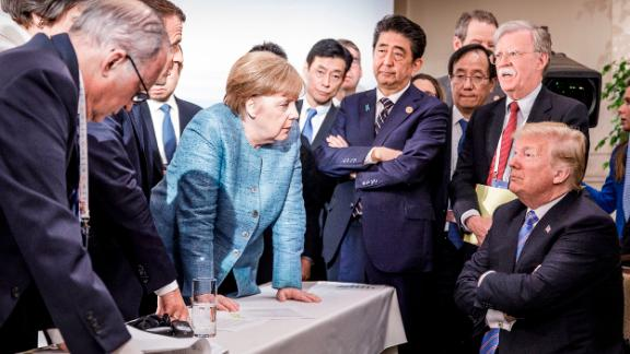 In this photo provided by the German Government Press Office, Merkel talks with Trump as they are surrounded by other leaders at the G7 summit in June 2018. According to two senior diplomatic sources, the photo was taken when there was a difficult conversation taking place regarding the G7's communique and several issues the United States had leading up to it.