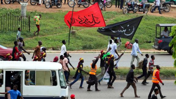 Members of Islamic Movement of Nigeria (IMN) wave flags and chant slogans as they take part in a demonstration to protest against the imprisonnement of a Shiite, in Abuja, on October 29, 2018. - The army and police confronted members of the Islamic Movement of Nigeria (IMN), the group