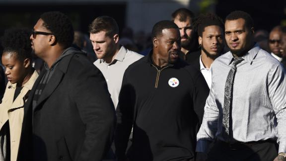 Members of the Pittsburgh Steelers stand with others Tuesday morning outside the Rodef Shalom Temple, where the services for the Rosenthal brothers were to be held.