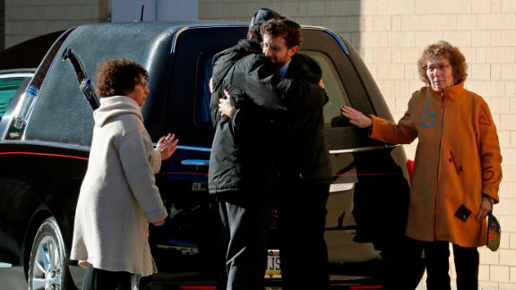 Mourners embrace after the hearse carrying the casket of Dr. Jerry Rabinowitz arrives Tuesday morning outside the Jewish Community Center in Pittsburgh.