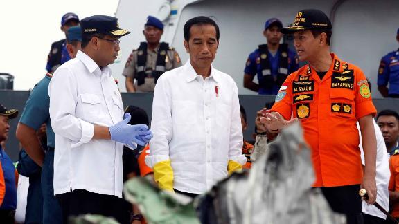 Indonesian President Joko Widodo inspects debris.
