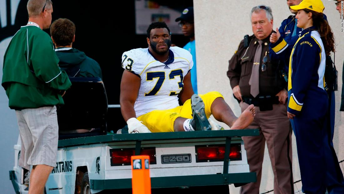 "Former Michigan Wolverine Maurice Hurst Jr. is carted off the field during a game against Michigan State in 2014.  ""It's a real tough duty being a college football player,"" he said, crediting the show ""All or Nothing: The Michigan Wolverines"" for an accurate portrayal of student-athletes."