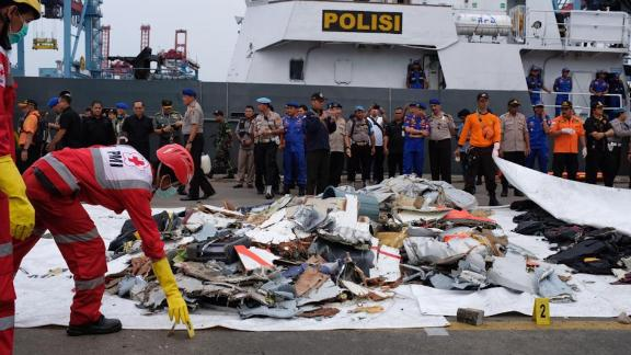 Search teams examine debris pulled from the sea near the crash site of Lion Air flight 610.