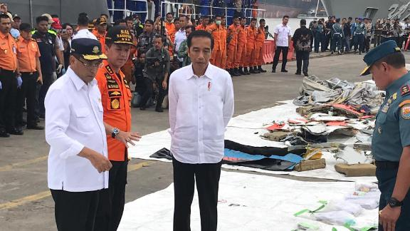 Indonesian President Joko Widodo, center, inspects debris recovered from the Lion Air flight 610 crash site on October 30, 2018.