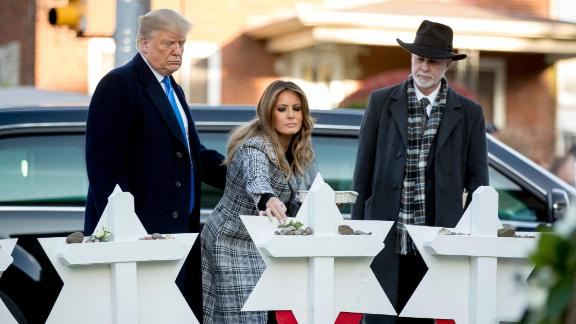 First lady Melania Trump, accompanied by President Donald Trump, and Tree of Life Rabbi Jeffrey Myers, right, puts down a white flower at a memorial for those killed at the Tree of Life Synagogue in Pittsburgh, Tuesday, October 30, 2018.