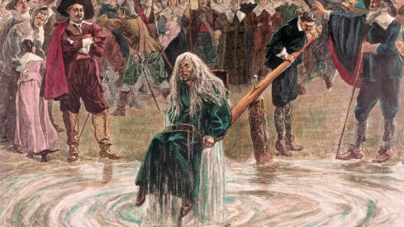 An accused witch going through the judgment trial, where she is dunked in water to prove her guilt of practicing witchcraft.