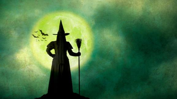 A Halloween witch dressed in black stands with her back to the camera as she holds her broom and is silhouetted by the rising full moon.  A colony of bats flies in the distance.