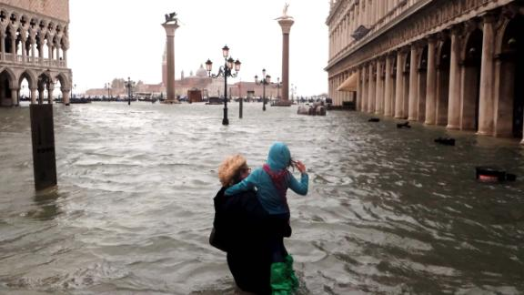 A woman holds a child as she walks in a flooded Saint Mark Square.