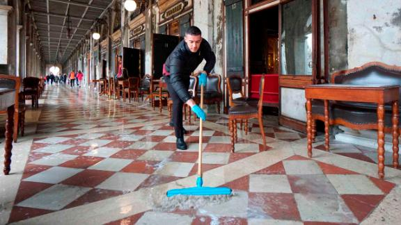 A man brushes away floodwater outside the historic Caffe Florian in St. Mark