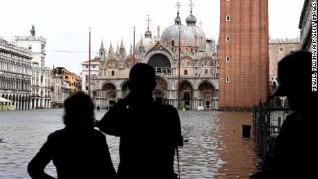 Tourists take pictures in the flooded St Marks Square during a high-water alert in Venice on October 29, 2018.