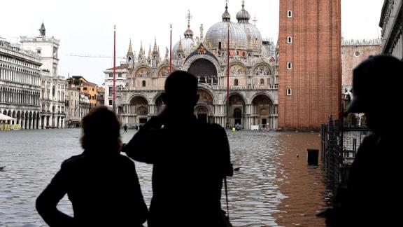 Tourists take pictures in the flooded St Mark Square during a high-water (Acqua Alta) alert in Venice on October 29, 2018. - The flooding, caused by a convergence of high tides and a strong Sirocco wind, reached around 150 centimetres on October 29. (Photo by Miguel MEDINA / AFP)        (Photo credit should read MIGUEL MEDINA/AFP/Getty Images)