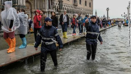Local police start to clear people from St. Mark's Square on Monday because of the flooding.