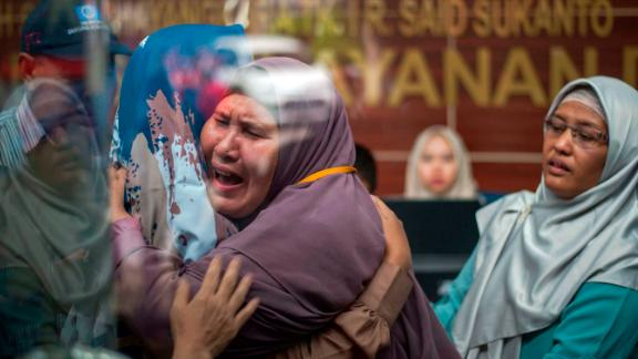 Victims' relatives embrace at a police hospital in Jakarta.
