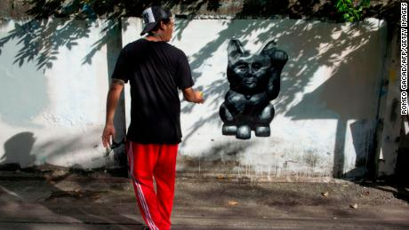 "The Thai street artist who goes by the name of ""Headache Stencil"" walks next to his graffiti caricature of Thailand's junta chief depicted as a ""lucky cat"" with paw raised to rake in money, spray-painted on a fence in Bangkok."