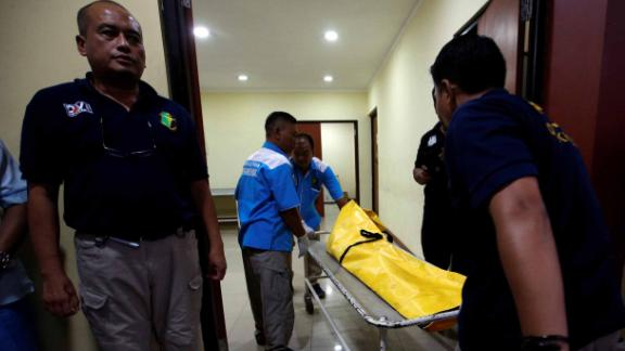 Officials transport a body bag in Jakarta.
