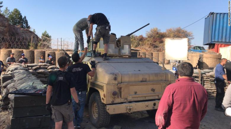 The film crew attend to an army tank on set.