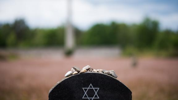 Pebble stones lie on a memorial stone at Bergen Belsen.