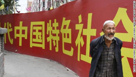 Photo taken on July 2, 2018, shows a man walking past a wall bearing a China Communist Party slogan in Kashgar in the country's Xinjiang Uyghur Autonomous Region.