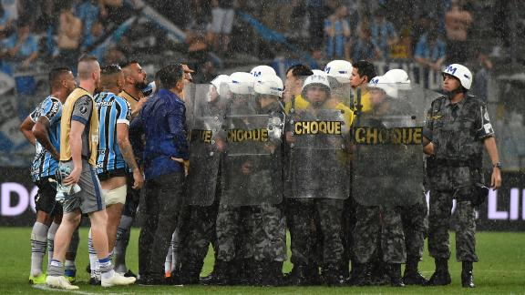 Riot police protect Uruguayan referee Andres Cunha from Gremio' footballers.