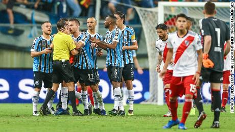 Matheus Bressan confronts referee Andres Cunha after receiving a red card.