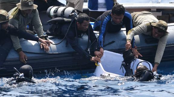 "An Indonesian Navy diver (bottom L) holds a recovered ""black box"" under water before putting it into a plastic container (R) after its discovery during search operations for the ill-fated Lion Air flight JT 610 at sea, north of Karawang in West Java on November 1, 2018. - One black box from the crashed Lion Air jet has been recovered, the head of Indonesia's National Transportation Safety Committee said on November 1, which could be critical to establishing why the brand new plane fell out of the sky. (Photo by ADEK BERRY / AFP)        (Photo credit should read ADEK BERRY/AFP/Getty Images)"