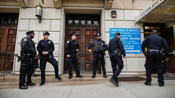 NYPD officers stand guard at the door of the Union Temple of Brooklyn on November 2, 2018 in New York City. - New York police were investigating anti-Semitic graffiti found inside a Brooklyn synagogue that forced the cancellation of a political event less than a week after the worst anti-Semitic attack in modern US history. (Photo by KENA BETANCUR / AFP)        (Photo credit should read KENA BETANCUR/AFP/Getty Images)