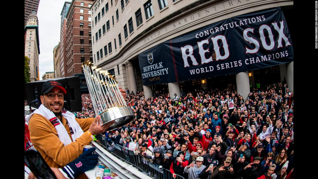 Mookie Betts of the Boston Red Sox displays the World Series trophy to fans during the rolling rally parade in Boston, Massachusetts. The Red Sox held the parade three days after defeating the Los Angeles Dodgers in the World Series.