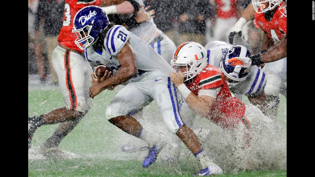 Miami defensive lineman Scott Patchan attempts to tackle Duke running back Mataeo Durant during the first half of an NCAA football game on November 3 in Miami Gardens, Florida. The Blue Devils defeated the Hurricanes 20-12.