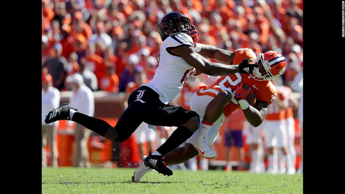 P.J. Blue of the Louisville Cardinals tackles Tavien Feaster of the Clemson Tigers during their game at Clemson Memorial Stadium on November 3, 2018 in Clemson, South Carolina.