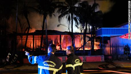 Firefighters try to extinguish a house set on fire in downtown Noumea overnight on November 5, 2018, after the results from an independence referendum in the French Pacific territory of New Caledonia.